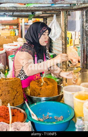 Phuket, Thailand 21st January 2019: Muslim woman serving spices at the town market. The markets is open early every day. - Stock Image