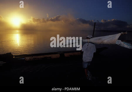 Fishing, fisherman going to work at sunrise, quiet sea landscape, early morning mist dissipating. Bahia State, Brazil. - Stock Image