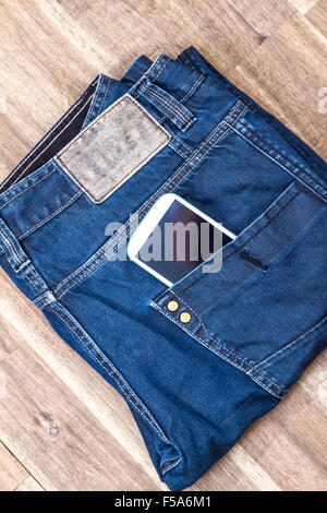 Jeans with cellphone in the pocket, background - Stock Image