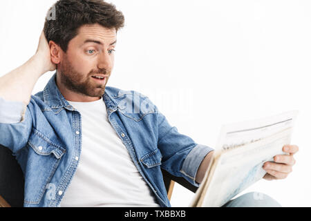 Portrait of a handsome bearded man wearing casual clothes sitting in chair isolated over white background, reading newspaper - Stock Image