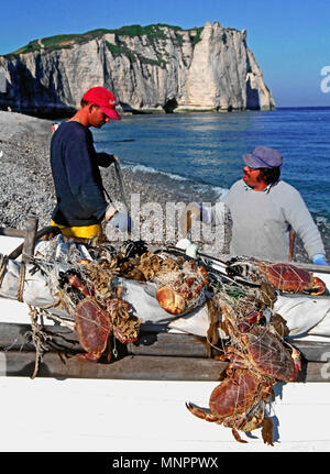 FISHERMEN WITH THEIR CATCH OF SHELLFISH. ETRETAT. NORMANDY. FRANCE. JUNE 2014. The iconic cliffs and the Arch Porte d'aval with the local fishermen an - Stock Image