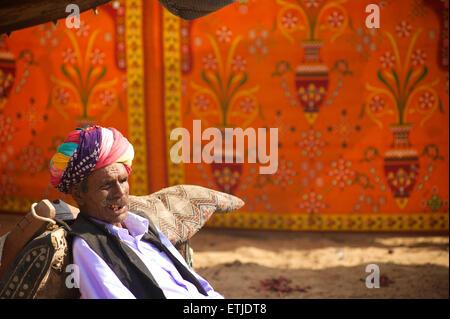 Rajasthani man relaxing at the Pushkar Camel Fair, Rajasthan, India - Stock Image