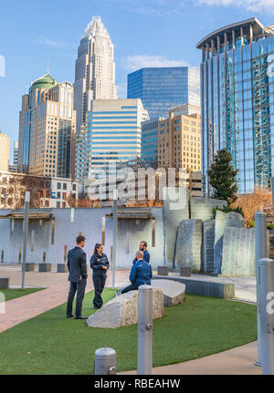 CHARLOTTE, NC, USA-1/8/19:  Four people, 3 men and one woman, stand in grassy area of Bearden park and socialize. - Stock Image