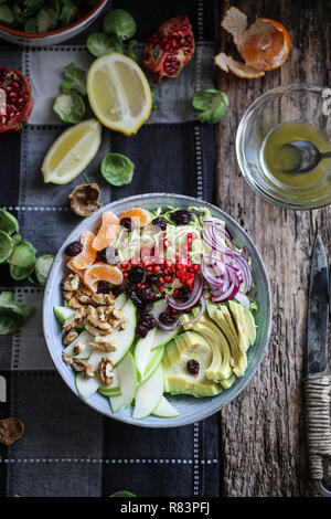 Brussel sprouts, avocado and green apple salad with pomegranate seeds and cranberries - Stock Image