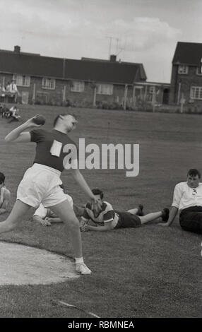 1960s, historical, school sport's day, schoolboy in shorts making a big effort as he attempts to throw or push the 'shot', the heavy weight in the shot put event, Englabd, UK. The shot put is a fantastic sport and recquires great technique as well as strength and has been in the modern Olympics since 1896. Said to have its origins from the 'putting the stone' competition in the Highland Games. - Stock Image