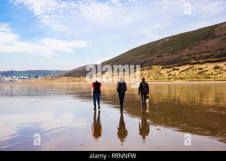 Three men with a dog reflected in wet sand walking on a quiet beach at low tide. Woolacombe, North Devon, England, UK, Britain - Stock Image
