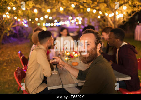 Portrait confident man drinking wine, enjoying dinner garden party - Stock Image