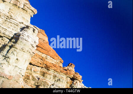 Whites orange and red hues in a desert rock face in the southern California Mojave Desert. - Stock Image