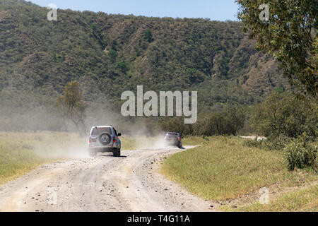 4x4 off road vehicles driving on dusty road, Hells Gate National Park, Kenya - Stock Image