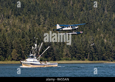 A fishing boat heads down the Wrangell Narrows as a float plane takes off above in the tiny village of Petersburg on Mitkof Island in Frederick Sound with the Alaska Coast Range of mountains behind on Mitkof Island, Alaska. Petersburg settled by Norwegian immigrant Peter Buschmann is known as Little Norway due to the high percentage of people of Scandinavian origin. - Stock Image