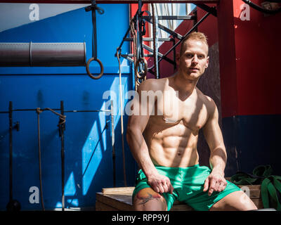 Handsome young man sitting on gym bench - Stock Image