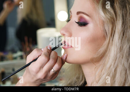 Make-up artist working in make-up studio, applying makeup on face of female clients. Makeup artist applies lipstick with brush. Evening make-up. Close - Stock Image