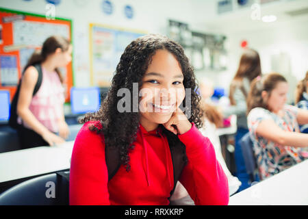 Portrait smiling, confident junior high school girl in classroom - Stock Image