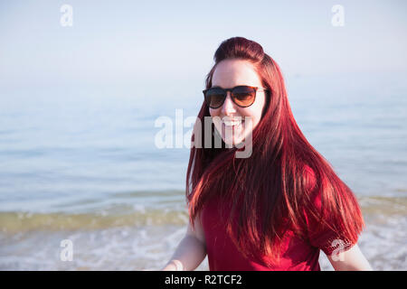 Portrait smiling, confident woman on sunny ocean beach - Stock Image
