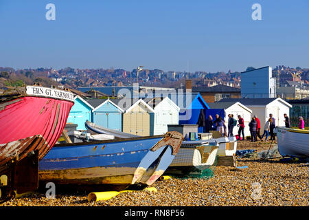 Old fishing boats and beach huts on the Bulverhythe beach, West St Leonards-on-Sea, East Sussex, UK - Stock Image