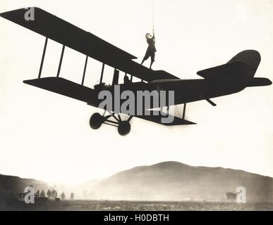 Stunt woman standing on top of biplane - Stock Image