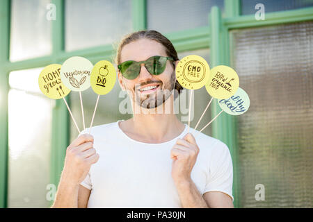 Handsome man holding green plates with healthy eating slogans outdoors on the green background - Stock Image