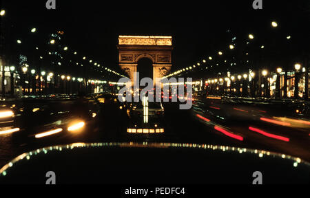 Paris France. The Arc de Triomphe and Champs-Élysées-Champs Elysees at night. 2000 The ceremonial arch stands at the top of the Champs-Élysées in Paris, it was commissioned by Napoleon to commemorate his victories in 1805–6. Inspired by the Arch of Constantine in Rome, it was completed in 1836. - Stock Image