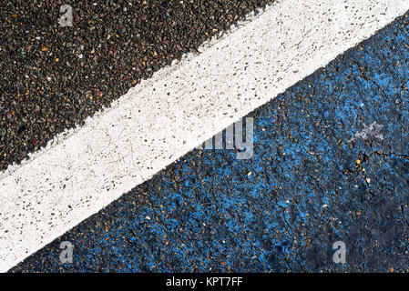 Single white road marking in diagonal composition with black bitumen and stone chipping edges - Stock Image