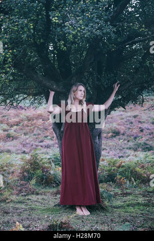 a blonde woman with a red dress is standing under a tree - Stock Image