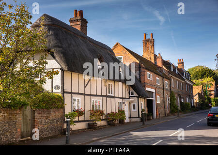 England, Berkshire, Streatley, High Street, Thatched Cottage in line of historic brick and flint faced houses - Stock Image