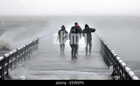 West Haven, CT USA-- A group of friends gets a closer look at the surging seas and high winds on a pier along the - Stock Image