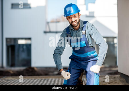 Funny portrait of a strong builder in uniform on the construction site with white houses on the background - Stock Image