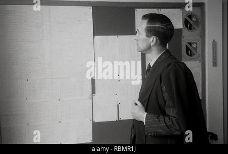 1950s, historical, Headmaster of the John Colet County Secondary school in a suit with gown looking at a noticeboard, England, UK. - Stock Image