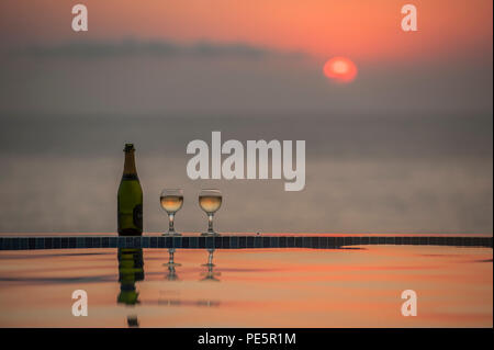 Champagne by an infinity pool as the sun sets - Stock Image