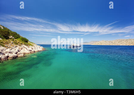 Crystal clear turquoise water in a lagoon near Bisti Beach on Hydra Island Greece. Unrecognizable people relaxing on a luxury yacht with mooring ropes - Stock Image