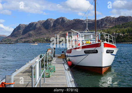 """Tourist boat """"Sula Mhor"""" tied up at landing stage on Loch Carron with distant crags in background - Plockton Village, Highland Region, Scotland - Stock Image"""