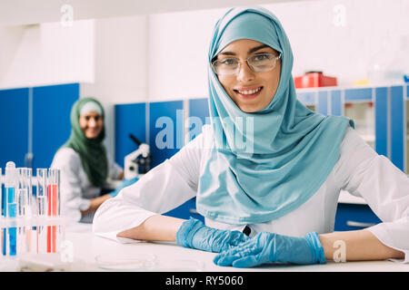 smiling female muslim scientist with test tubes looking at camera during experiment in chemical lab - Stock Image