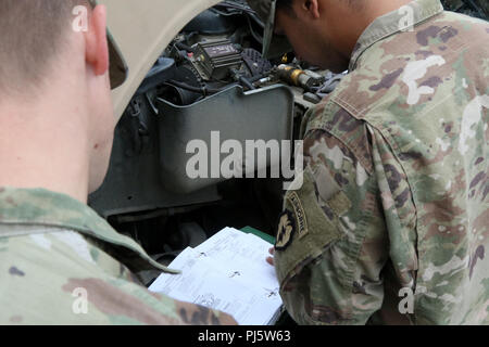 Paratroopers with 6th Brigade Engineer Battalion refer to their vehicle's technical manual as they conduct preventative vehicle-maintenance checks 27 Aug., 2018, at Joint Base Elmendorf-Richardson, Alaska. The manuals provide step-by-step instructions, giving paratroopers a quick reference to ensure all inspection points were done correctly. (U.S. Army photo by Sgt. Alexander Skripnichuk) - Stock Image