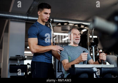 A senior man with a young trainer doing strength workout exercise in gym. - Stock Image