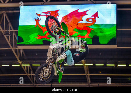 A motor bike rider jumps pulls a trick in front of an image of the Welsh flag at the launch of the Nitro World Games freestyle motor cross event, at the Principality Stadium in Cardiff, as it was announced that Nitro World Games will be held in Wales in 2020. - Stock Image