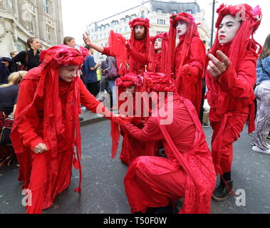 London, UK. 19th Apr, 2019. Performers seen in fancy costumes in the crowd during the demonstration.Environmental activists from Extinction Rebellion movement occupy London's Oxford Circus for a 5th day. Activists parked a pink boat in the middle of the busy Oxford Circus road junction blocking the streets and causing traffic chaos. Credit: Keith Mayhew/SOPA Images/ZUMA Wire/Alamy Live News - Stock Image