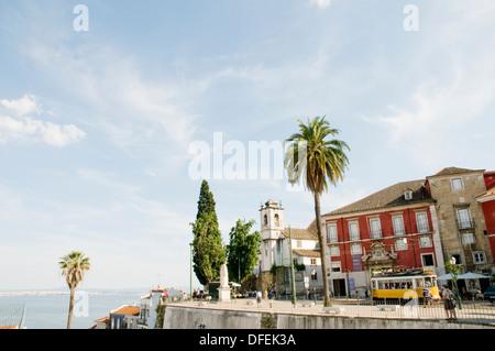 The No 28 tram pulling up at a stop on Largo das Portas do Sol, next to the Museu de Artes Decorativas, in Lisbon.  - Stock Image