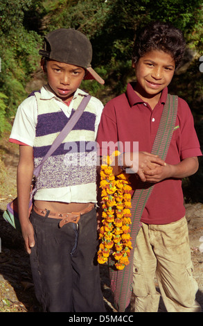 Two school boys one with Marigold flower garland on track on Annapurna Circuit Nepal Himalayas - Stock Image