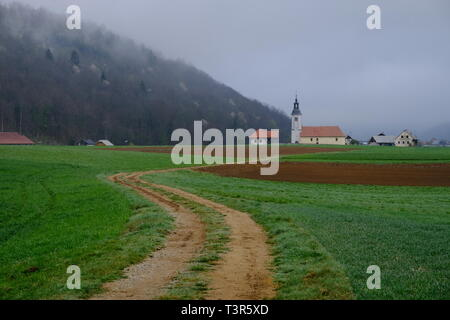 Slovenian village and end of curvy dirt road, with church sitting at foot of hill on a foggy morning - Stock Image
