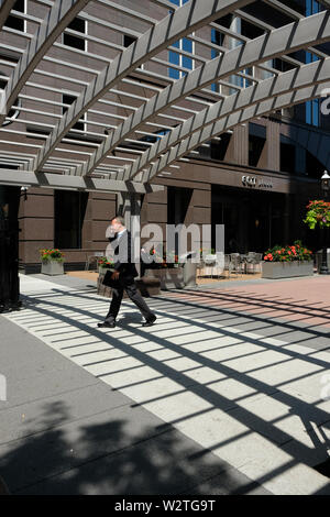 A business man in a suit walks under shadows cast from an overhead latticework roof in EQT Plaza, downtown Pittsburgh, Pennsylvania, USA - Stock Image
