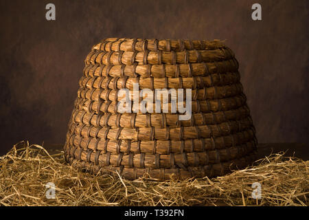 Antique beehive wicker basket on a brown rustic background - Stock Image