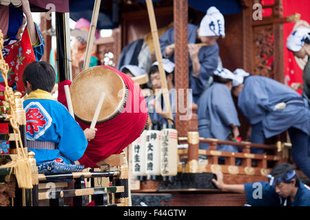 Boy playing taiko drums flute players on traditional Japanese floats - Stock Image
