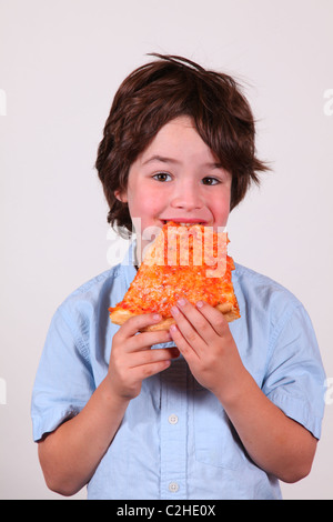 Boy taking a bite out of a slice of cheese pizza - Stock Image
