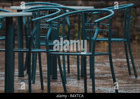 A shot at several green metal chairs in the rain - Stock Image