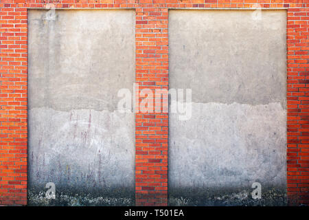 weathered stucco wall and red brick frame around. - Stock Image