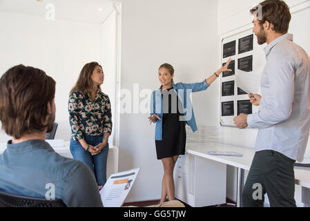 Happy businesswoman giving presentation to her colleagues - Stock Image