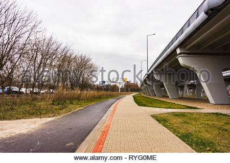 Poznan, Poland - March 3, 2019: Footpath and bike route next to a bridge on a cloudy day. - Stock Image