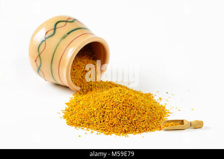 Heap of bee pollen granules, a wooden scoop and an overturned glazed clay pot full of pollen. Selective focus. Closeup. - Stock Image