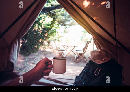 view of a hand of a hiker person resting with a cup in a camping tent, travel discovery concept, point of view shot - Stock Image
