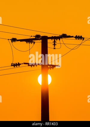 Sunrise and silhouette of power pylon, France. - Stock Image